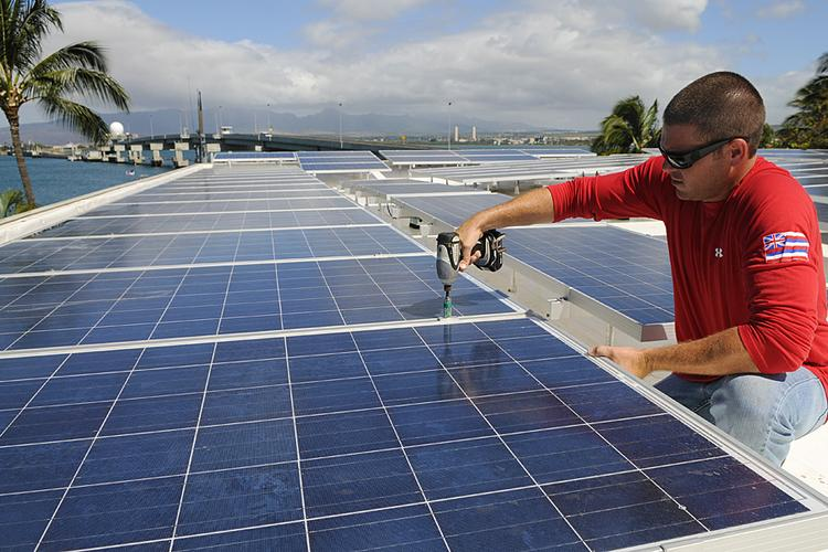 A solar installer installs photovoltaic panels on a roof near Pearl Harbor in Hawaii.