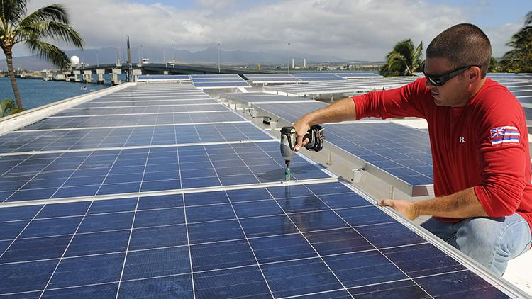 A solar installer installs photovoltaic panels on a roof near Pearl Harbor in Hawaii in this file photo. Hawaii was sixth in solar megawatt rankings by the Solar Electric Power Association's latest Utility Solar Rankings.
