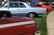 A line of cars at the Niello Concours at Serrano includes a Chevrolet Impala SS, a Pontiac GTO and a Ford Mustang.