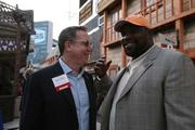 Bryan Glazer, executive vice president of The Tampa Bay Buccaneers, visits with former Buccaneer Warren Sapp.
