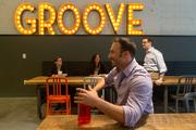 Ryan MacMurray, a front-end developer at Groove Commerce, chats with colleagues in the company's new office cafe.