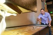 Ryan MacMurray, a front-end developer at Groove Commerce, plays an arcade game in the company's new office cafe.