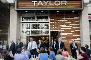 President Barack Obama, center, greets patrons while exiting a Taylor Gourmet Deli in D.C.