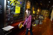 """Meka Manchak, exhibits coordinator at MOHAI, demonstrates an exhibit still under construction called """"Cities Ignite,"""" which shows that good ideas grow when people come together."""