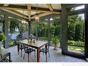 The Lake Minnetonka mansion has a screened-in, beamed porch next to the lake.