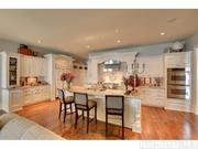 The gourmet kitchen features antique ivory cabinetry.