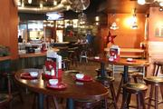 Heavy wood tables and stools are the furniture of choice at Drake's. Red plates accent table settings.