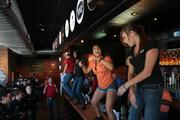 (From left) Brandon Crawford, Rockey Hayes, training coordinator Megan Fulker and Stephanie Hafer pump up the enthusiasm of the newly hired staff as they dance on the bar.