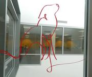 A silhouette of a cat on the glass atrium.