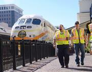 Engineer Fredrick Robillard and Conductor Robert Ortiz take a break before visitors arrive to view their new ride.
