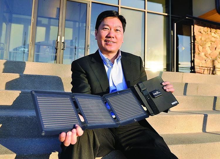 Victor Lee, CEO of Thornton's Ascent Solar Technologies Inc., with a EnerPlex Kickr IV, a flexible solar power panel for charging small electronic equipment.