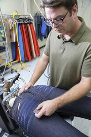 "Jason Napier, engineer at Wrangler, demonstrates hand sanding a disstressed ""whisker"" pattern on a pair of jeans. This is one of several ways to create the pattern by hand."