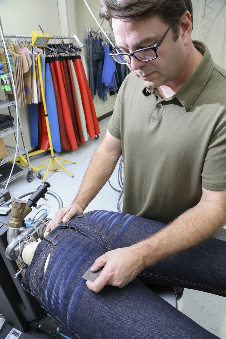 "Jason Napier, engineer at Wrangler, demonstrates hand sanding a disstressed ""whisker"" pattern on a pair of jeans. This is one of several ways to create the pattern by hand. Companies like VF Corp. and Wrangler are squarely focused on jeanswear innovation."
