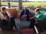 Anita Chartier and Larry and Cindy Tompkins chat with wine on the patio overlooking the vineyard.