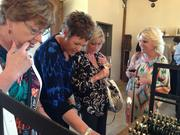 Anita Chartier, Gretchen Roy, Susie Anderson and Rachel Allen review the olive oils available for purchase at Round Pond.