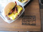 The SmokeShack is a cheeseburger with Nimon Ranch applewood-smoked bacon and hot cherry peppers. ShakeShack's tables, like this one on the second floor, are crafted in Brooklyn, N.Y., out of wood reclaimed from a bowling alley.