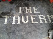 Floor tiles in one of the storefronts at 207 Broadway reveal one of the former tenants. The Tavern was in business from 1934 to 1979. Today, just one storefront has a tenant, Broadway News.