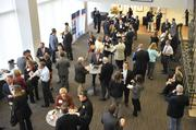 Attendees network before the CREQ Live event at the UNC Charlotte Center City Campus.