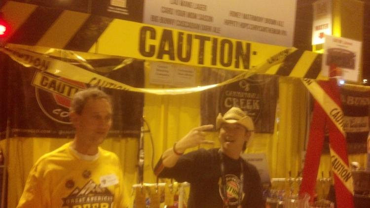 Caution Brewing Co. co-owner/brewer Danny Wang, celebrates the company's success at his booth at the 2013 Great American Beer Festival.