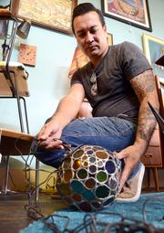 Steve Settle of Atomic Junkies sets up a lead lamp display in the furniture showroom.