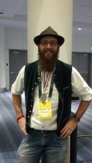Adam Draeger, head brewer at Yak & Yeti Restaurant & Brewpub, displays the silver medal he won for his Chai Milk Stout at the 2013 Great American Beer Festival.