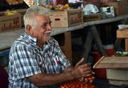 Gabriel Ragel, 74, works at his produce booth in the Beaver Street Farmers Market on Friday, Oct. 11, 2013.  Ragel has been working at the market for 16 years.