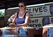 Charlotte Tzabari pours olives at her booth in the Beaver Street Farmers Market on Friday, Oct. 11, 2013.