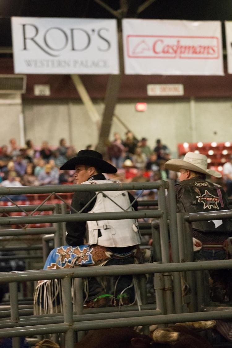 Bull riders await the start of competition on Friday at the Ohio Fairgrounds, under the banners of a couple of the event's many sponsors.