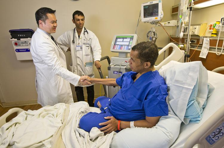 Drs. Richard-Tien Ha and Dipanjan Banerjee of Stanford Hospital and Clinics cardiology department check in on Vaness French, the second patient ever to receive a total artificial heart transplant from the hospital. French is in the hospital longer than he expected due to the government shutdown.