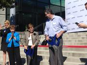Yodle CEO Court Cunningham, right, cuts a ribbon with Charlotte Mayor Patsy Kinsey, center, and Mecklenburg County Commission Chairman Pat Cotham.