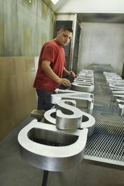 Fastest-growing Private Companies 2013 - Flight IV, No. 3: BSC Signs Joe Landin, painter/fabricator, gets ready to paint letters for a sign at BSC Signs.