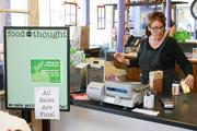 Melinda Foley staffs a checkout at her store, Food For Thought, which is holding a liquidation sale and plans to close later this month.