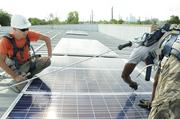 Texas Solar Outfitters employees installing a 100kW system on the roof of K&N Sales at 1401 Shepherd Dr.