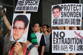 Protesters hold placards outside government headquarters during a rally in support of Edward Snowden, the former National Security Agency contractor, in Hong Kong, China, on Saturday, June 15, 2013. Snowden was eventually flown to Russia, where he now lives.