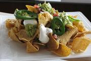 The Mucho Nachos, with sour cream, guacamole, salsa, pico of the month, onions and grilled fresh jalapeno peppers.