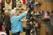 A woman checks out the shoes at the Morganton Belk.