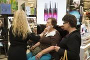 A shopper enjoys a makeover at the opening of the Belk store in Morganton.