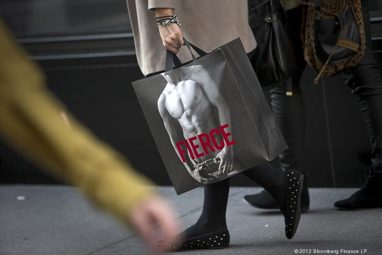 "A shopper wearing black studded flats carries an Abercrombie & Fitch Co. bag displaying the word ""Fierce"" after exiting a store in New York. Abercrombie & Fitch Co. is scheduled to release earnings data tomorrow."