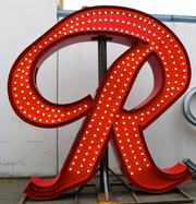"Western Neon is finishing a 12-foot-tall replica of the Rainier ""R,"" to be placed back atop the old Rainier Brewery on Oct. 24. The replica R will have a few updates: For one, it will have lights and neon on both sides; the original only had lights on one side."