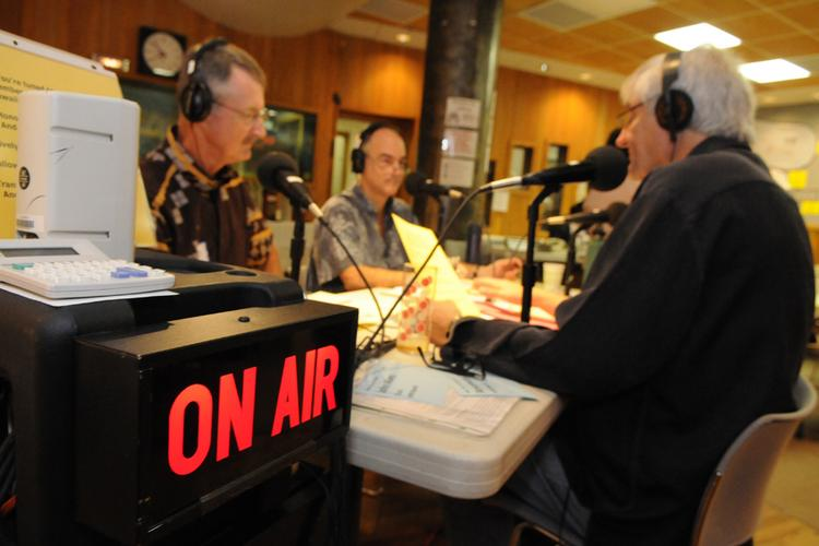 From left, Hawaii Public Radio boardman Jack Laufer and News Director Bill Dorman, talk with President and General Manager Michael Titterton during HPR's fall pledge drive on Wednesday, Oct. 16, 2013.