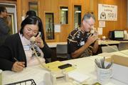 From left, Hawaii Public Radio board members Marcie Ueara Herring and Jack Laufer answer phones during the first day of HPR's fall pledge drive.