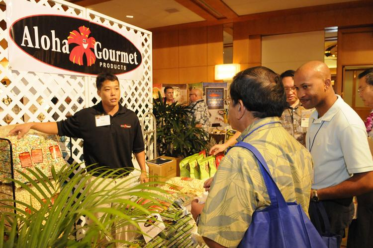 Ryan Okamura, sales manager for Aloha Gourmet Products ,talks with Navy Exchange and commissary buyers at the American Logistics Food Show at the Hawaii Prince Hotel.