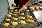 Employee Jimmie Ellington removes corn bread muffins from a cooking tray.