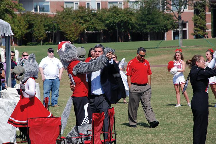 Mike Lipps, GM of LexisNexis's Cary-based division, enjoys a dance with Mr. Wuf at an NCSU game.