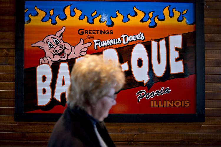 A customer passes a Bar-B-Que sign hanging in the lobby of a Famous Dave's of America.