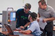 From left, students Dean Stilianos, left, and Kurt Stapleton, center, work on a computer numeric controlled simulator in a machine operations class at the Workforce Development Center at Cincinnati State and Technical College. At right is class instructor Jeff Smith.