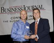 Lance Loveday, owner of Closed Loop, accepts an award from Sacramento Business Journal Publisher Terry Hillman. Closed Loop won second place in the micro companies category at the Business Journal's Best Places to Work awards Tuesday.