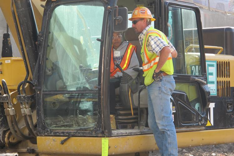 Tim Butler of Edgerton Contractors helps a student through maneuvers.