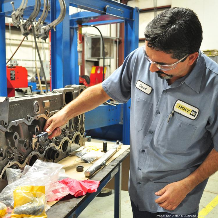 A Holt employee works on an engine.