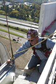 Greg Meredith with Pioneer Glazing & Caulking Is on a ledge nine floors up working on windows.